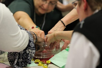 Sisters of Providence and Providence Associates gathered dip their hands into a bowl of water and bless themselves.